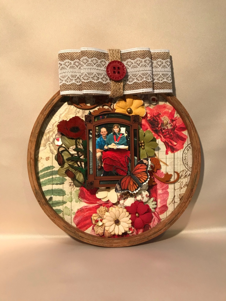 A wooden hoop made into a photo and flower wall hanging
